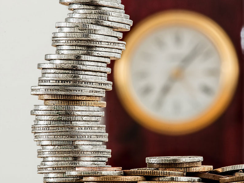 Pile-of-coins-with-blurred-clock-in-background